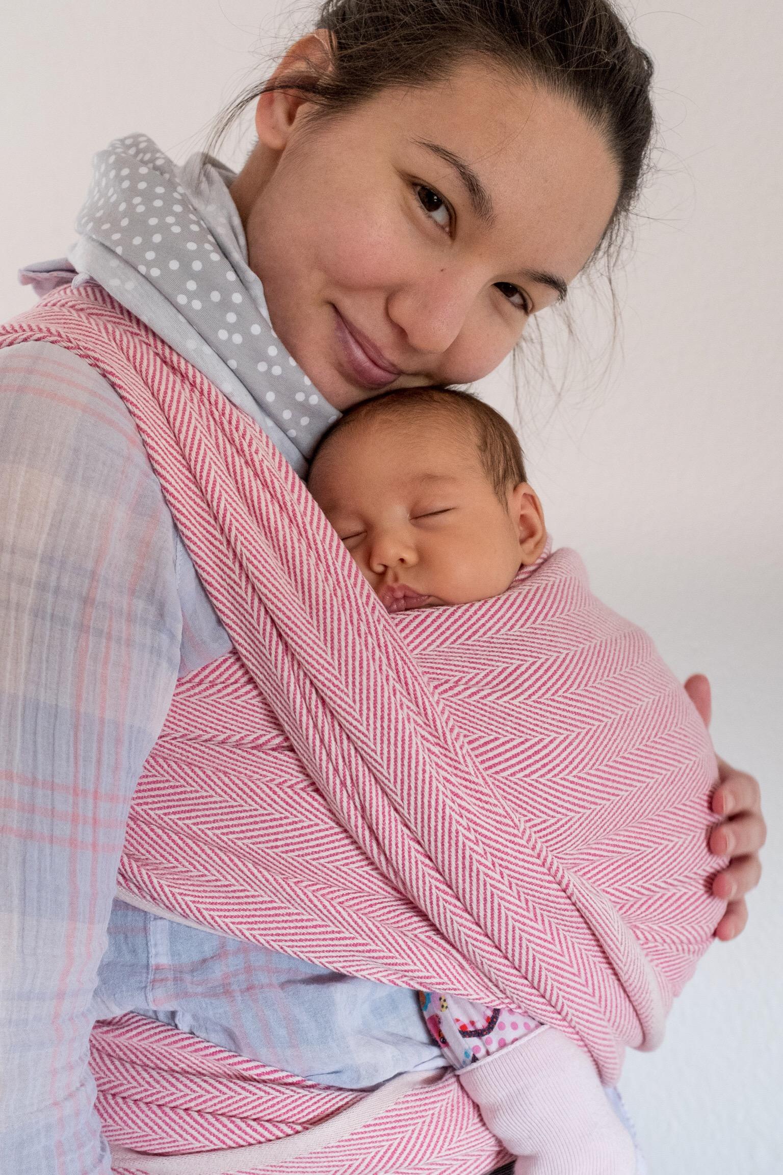 Ich trage mein Baby in dem rot-weißen Didymos Lisca Tragetuch.