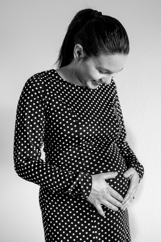 Frau in einem gepunktetem Kleid mit Babybauch.